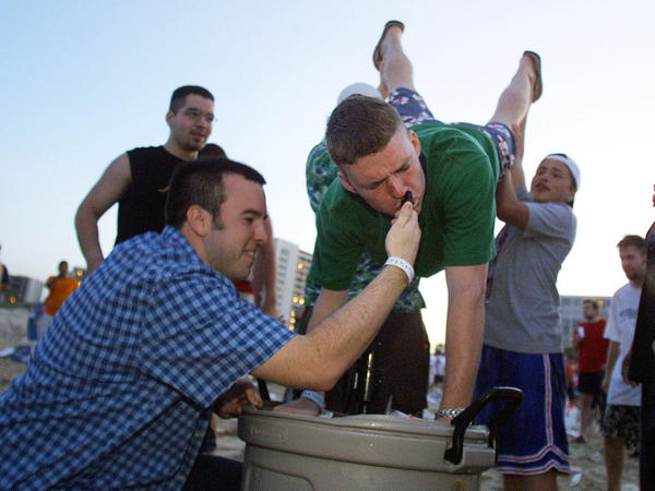 College students aid a colleague as he performs a keg stand in this file photo. Princeton Review released its new list of top party schools in America Monday.
