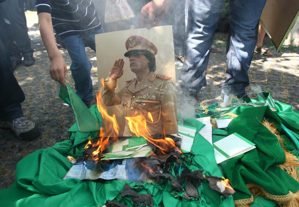 Protesters burn a portrait of Libyan leader Moammar Gadhafi and copies of his Green Book outside the Libyan Embassy in Ankara, Turkey, on Monday.