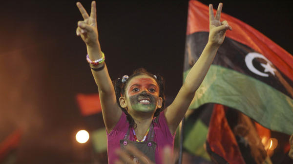 A young Libyan in Benghazi celebrates Tuesday over news that Moammar Gadhafi's rule appears to be at an end. The U.S. says it is prepared to unfreeze Libyan assets quickly and make them available to a new government.