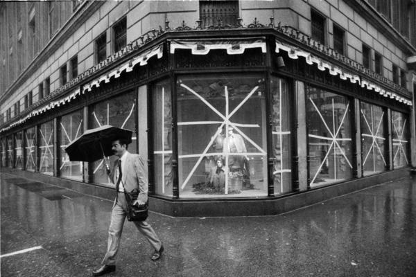 An unidentified man carries an umbrella as he walks in the rain past Saks Fifth Avenue in New York City in September 1985.  The windows of Saks had been taped up as the city braces for the arrival of Hurricane Gloria.