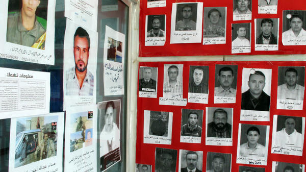 The walls of the Libyan Red Crescent office in Benghazi, Libya, shown here on Monday, are covered with photos of the missing. Some disappeared during Libya's revolution, but some have been missing for more than 10 years. Now, thousands released from Libya's prisons are being reunited with their families.