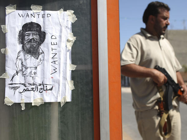 A rebel fighter patrolled near a homemade wanted of Moammar Gadhafi at a checkpoint in Tripoli, Libya, on Tuesday.
