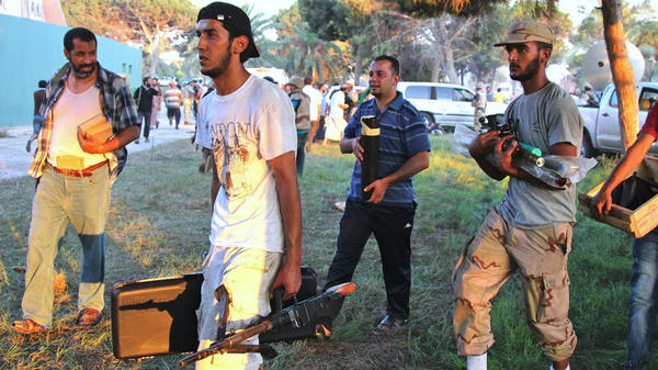 Libyans take weapons from Moammar Gadhafi's compound in Tripoli last month. There are concerns that looted weapons could contribute to instability in Libya as the country tries to establish a new government.