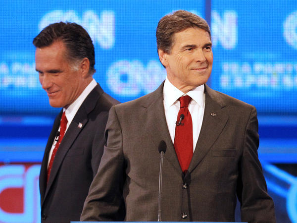 Republican presidential candidate former Massachusetts Gov. Mitt Romney (left) passes behind Texas Gov. Rick Perry during a break in a Republican debate Monday in Tampa, Fla.