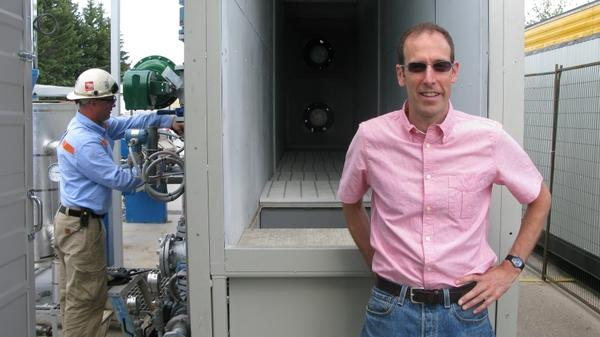 David Keith (right) stands in front of his air capture prototype on the University of Calgary campus.