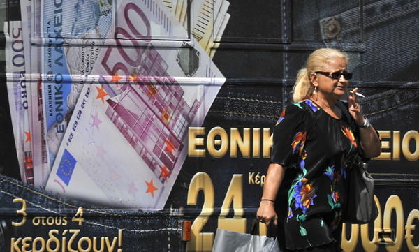 """A woman walks past an advertisement of the national lottery in Athens. Public outrage over austerity measures is intense, and a new levy on real estate has been dubbed the """"monster tax."""""""