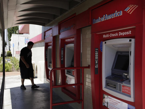 <p>A man walks up to an ATM outside a Bank of America branch in Los Angeles. Bank of America has said it will charge customers a $5 monthly fee to use its debit card — a plan that has set off grumbling from consumer advocates at the highest levels.</p>
