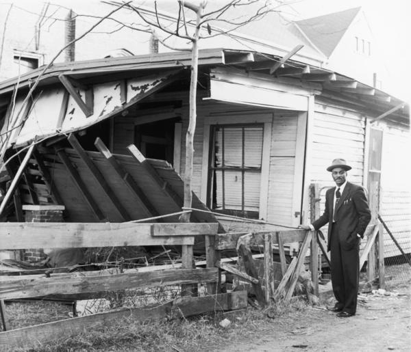 <p>In this undated photo, Shuttlesworth stands near his Birmingham home after it was bombed. </p>