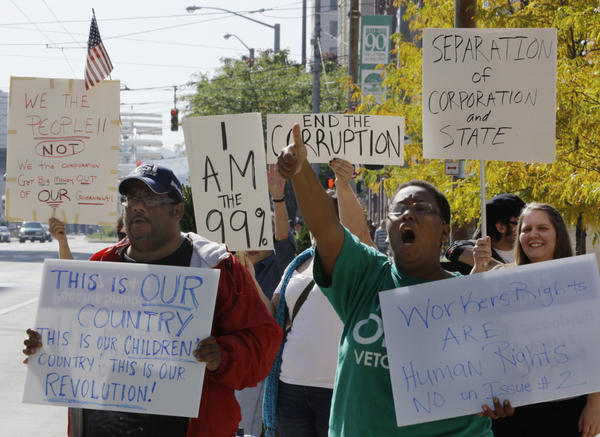 <p>Protesters organized by Occupy Wall Street and Occupy Together yell slogans and hold signs at Courthouse Square in Dayton, Ohio, Wednesday. Several large unions have come out in support of Occupy Wall Street.</p>