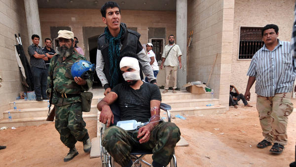 <p>On a morning of fierce street fighting, a wounded man is wheeled into a field hospital outside Sirte. The city was rocked by explosions, and Libyan National Transitional Council fighters were targeted by pro-Gadhafi snipers.</p>