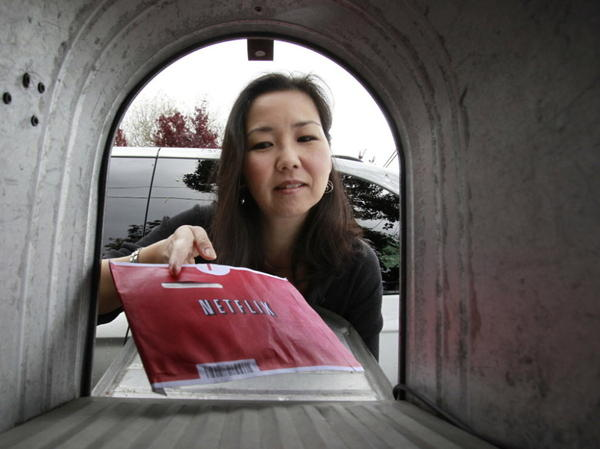 <p>Carleen Ho picked up a Netflix movie from her mailbox in Palo Alto, Calif. The company announced Monday that it will not split its streaming and DVD video offerings.</p>