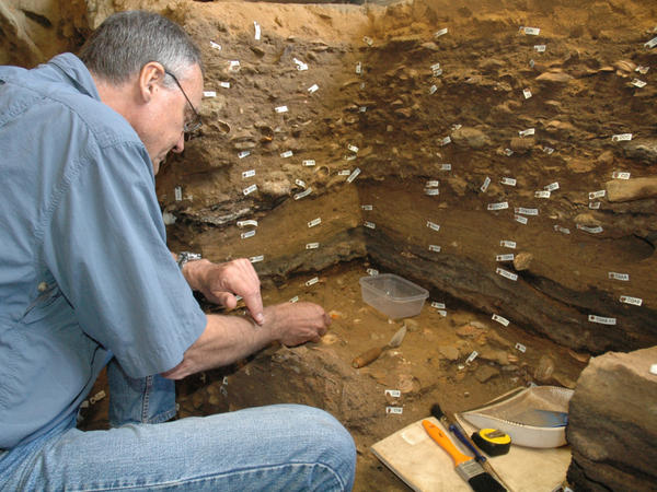 <p>Archaeologist Christopher Henshilwood excavates at the 100,000-year-old levels of the Blombos cave in South Africa.</p>