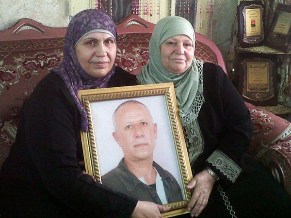 "<p>Faizeh al-Maslamani (left) with her sister and a portrait of her husband, Ali, due to be released with more than 470 Palestinian prisoners Tuesday. Ali spent most of the past three decades in an Israeli jail. Faizeh says he has 10 grandchildren he's never seen. She hopes he'll accept ""a life sentence in the house.""</p>"