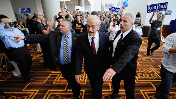 <p>Republican presidential candidate Ron Paul is escorted to a ballroom to speak to his supporters during the California Republican Party Convention this September in Los Angeles. The Texas congressman was once a small-town doctor who specialized in delivering babies. </p>