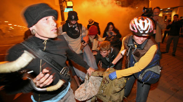 <p>Occupy Oakland protesters carry away a man who was hit by a police tear gas canister Tuesday near the Oakland City Hall.</p>