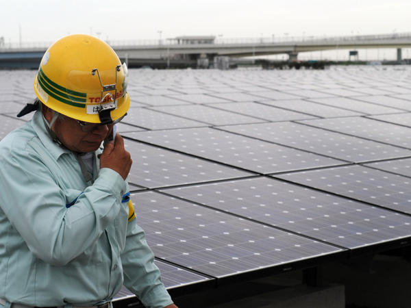 <p>A worker stands next to an array of Sharp solar cell modules at a power plant south of Tokyo in August. Sharp was one of 1,400 solar panel manufacturers in attendance at the Solar Power International conference, where industry optimism was high.</p>