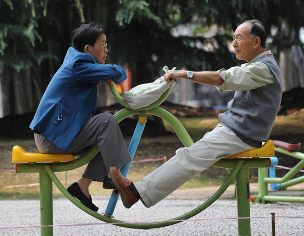 An elderly Chinese man and woman chat at a park in Shanghai. Hundreds of elderly Shanghai residents make their way to IKEA twice a week for an informal lonely hearts club.