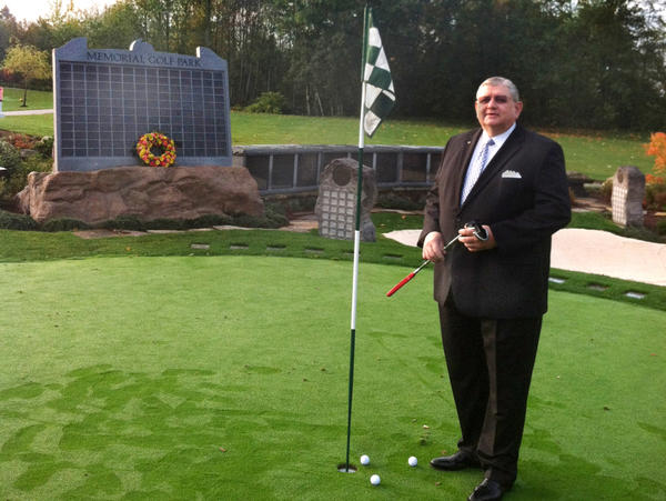 """<p>Memorial Golf Park creator Arne Swanson stands on its putting green — an ossuary with enough capacity to hold 600 former avid golfers. Families can purchase a spot on the solemn """"leader board"""" to preserve the loved one's standing for all eternity. </p>"""