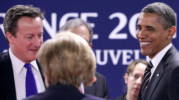 British Prime Minister David Cameron (left) speaks with German Chancellor Angela Merkel and President Obama at the G-20 summit Friday in Cannes, France.