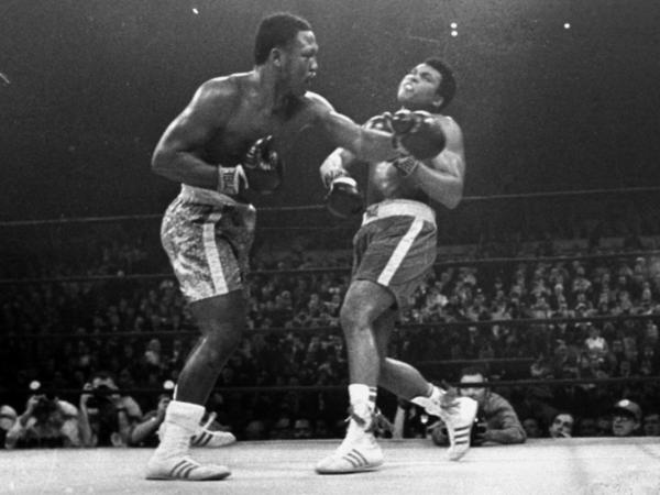 "Joe Frazier (left) hits Muhammad Ali during the 15th round of their heavyweight title bout — the ""Fight of the Century"" — at New York's Madison Square Garden in March 1971."