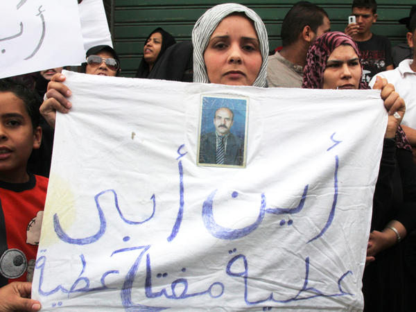 "A woman outside the Hudba el-Gassi compound in Tripoli, Libya, holds up a sign asking, ""Where's my father?"" Once a military police base, Hudba el-Gassi is now a makeshift prison for regime loyalists and others rounded up by armed militiamen."