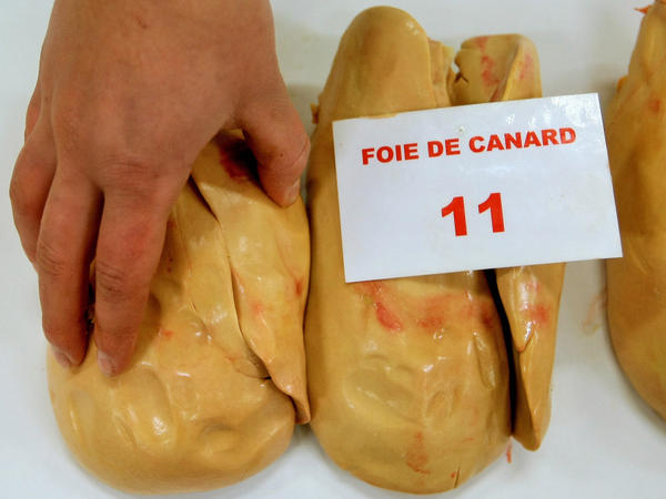 A jury member feels a piece of duck foie gras during a contest of local producers and producers from southwestern France.