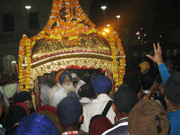 Devotees reach out to the gilded litter that carries the Sikh holy book, the Guru Granth Sahib, to the Golden Temple in Amritsar.