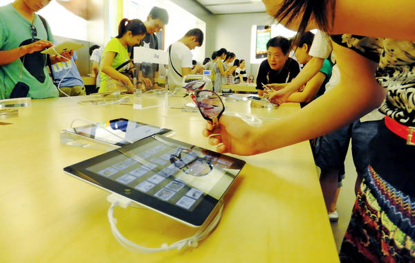 Customers look at iPads at an Apple Store in Shanghai, China. Some goods made in China cost more there than they do abroad.