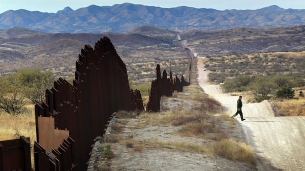 A Border Patrol agent looks for footprints from illegal immigrants crossing the U.S.- Mexico border in 2010. Traffickers have begun using immigrants as drug smugglers, recruiting voluntarily and forcibly.
