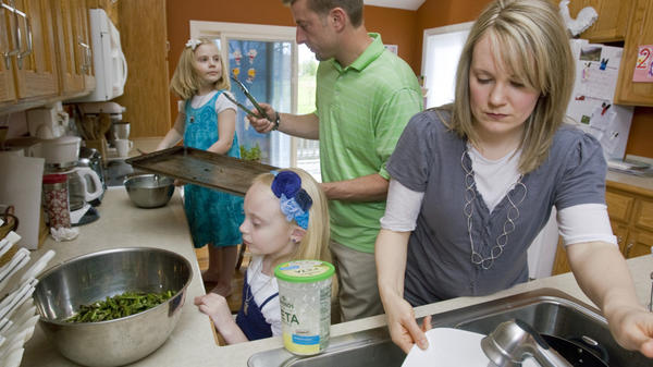 A Kansas City family prepares a meal together. A new study finds that working mothers log more hours — and get more stressed — than working fathers while multitasking at home. (This family wasn't part of the research.)