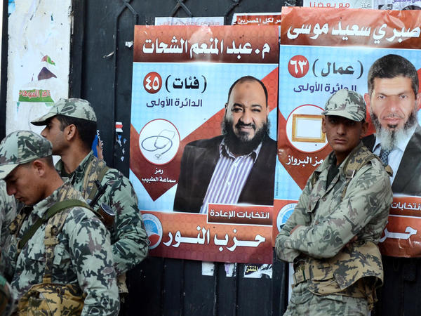 Egyptian soldiers stand in front of campaign posters for candidates from the hard-line Islamist Salafist Al-Nour party, in the coastal city of Alexandria.