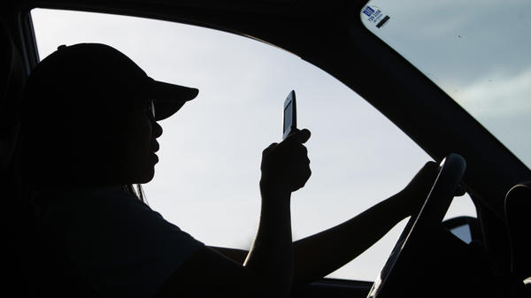 A driver uses a cellphone in Maine, which has laws that ban people under 18 from using cellphones behind the wheel and bar all drivers from texting.