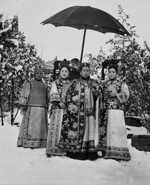 Cixi, accompanied by her attendants, stands in the snowy gardens of Wanshoushan (Longevity Hill), the central hill of the Summer Palace. The image is one of nine similar photographs that were most likely taken for the enjoyment of the empress and her attendants — not for any diplomatic purpose.