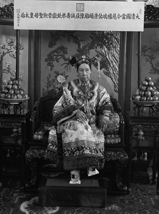 "This photograph is one of a series of photos that shows Cixi seated on her throne in front of a banner that declares her full title. <a href=""http://media.npr.org/assets/artslife/arts/2011/12/cixishoes_custom.jpg"">Click here to see a close-up</a> of her ""horse-hoof"" platform shoes."