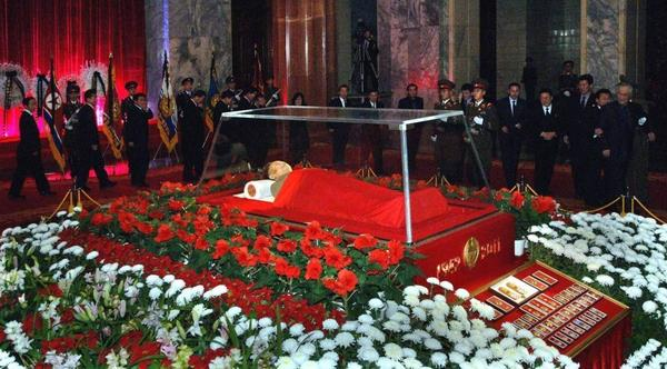 The body of North Korean leader Kim Jong Il is seen as people pay their respects in Pyongyang on Dec. 20. South Korean analysts say power in the North is likely to be vested in a new leadership group, with Kim's son Kim Jong Un as its public face.