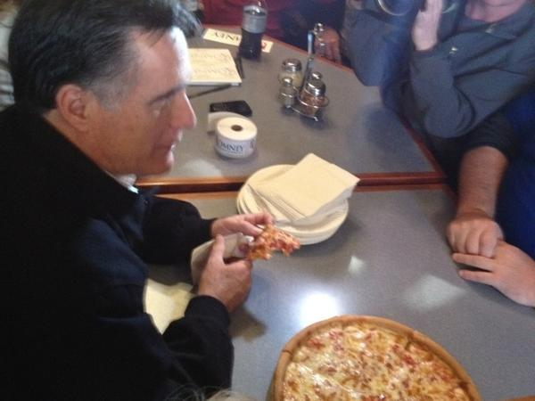 Romney eats a slice of pizza — this one with the cheese still on — at a campaign stop in Newport, N.H