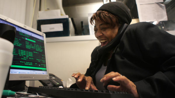 Louise Tucker-Mitchell laughs on the phone with a customer at Enterprise Rent-A-Car at Reagan National Airport in Washington, D.C. She says she likes working the week between Christmas and New Year's, as it's calmer and a good time to catch up.