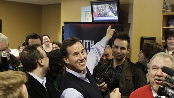 Republican presidential candidate Rick Santorum points to a television showing his campaign stop on live at the Daily Grind coffee shop in Sioux City, Iowa, Sunday.