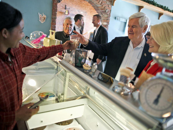 Former House Speaker Newt Gingrich, with his wife, Callista, buys two scoops of Moose Tracks ice cream at Elly's Tea and Coffee House in Muscatine, Iowa, on Tuesday.