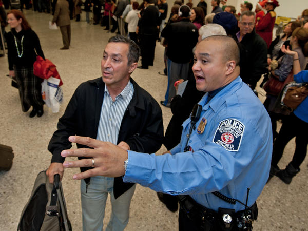 A police officer directs travelers arriving at Dulles International Airport. Some think the passenger experience hasn't been very good overall, and is unlikely to improve in the new year.