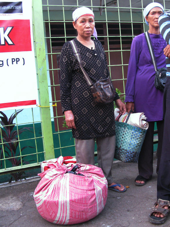Fruit vendor Mina, who uses just one name, waits for a train home with her merchandise wrapped in a pink cloth.