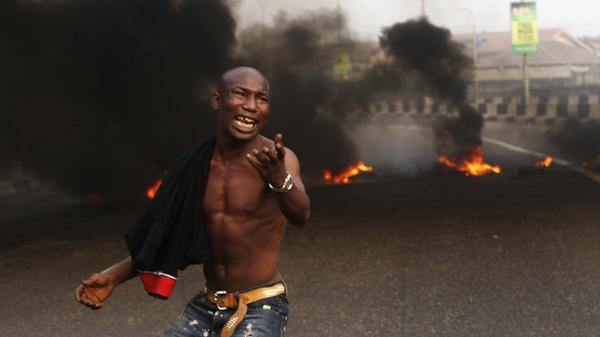 The Nigerian government removed fuel subsidies, which drove up prices and prompted nationwide strikes this week. Here, a young man protests in front of burning tires in the commercial capital Lagos on Tuesday.