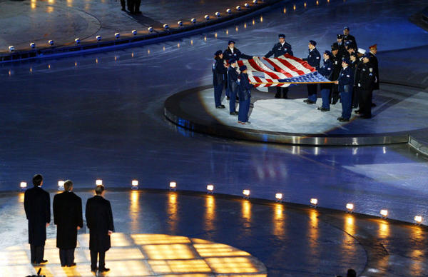 At the opening ceremony of the 2002 Winter Olympics in Salt Lake City, Mitt Romney (left) stands with President George W. Bush (center) and International Olympic Committee President Jacques Rogge (right) in front of the American flag that flew at the World Trade Center before the Sept. 11 terrorist attacks.