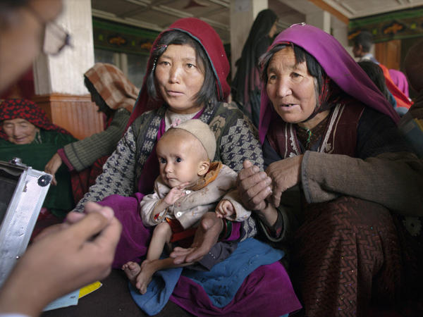 Dr. Mohammed Rashidi talks to a mother about her severely malnourished baby at a makeshift mobile health clinic in a remote village in Afghanistan's Bamiyan province last year.