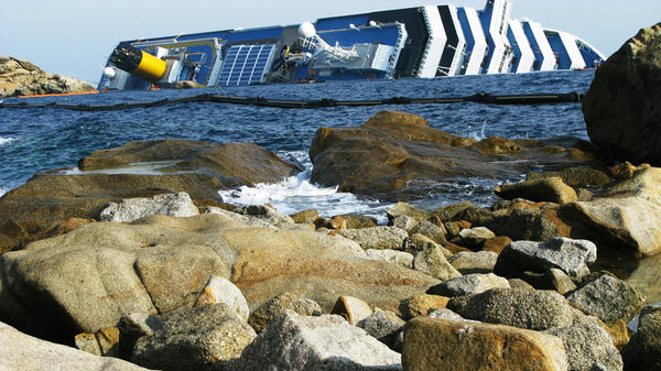 The Costa Concordia cruise ship remains half-submerged three weeks after it crashed. It continues to be a source of anger for local residents.