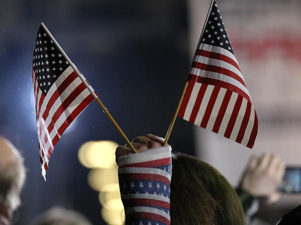 An attendee holds American flags during a rally Saturday in Colorado Springs, Colo. The rally was for Republican Mitt Romney, but a new study says the number of newly declared independents is outpacing new registration for either Republicans or Democrats in the state.