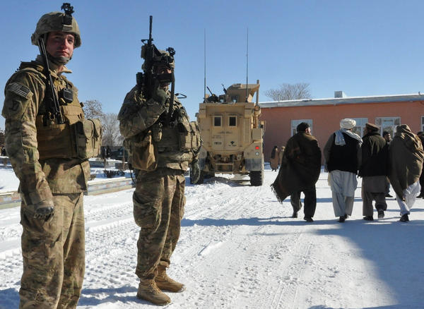 Afghan men walk past American soldiers in Ghazni province on Thursday. U.S. and Afghan officials are in talks that will determine how many American troops stay in Afghanistan after the NATO mission ends in 2014.