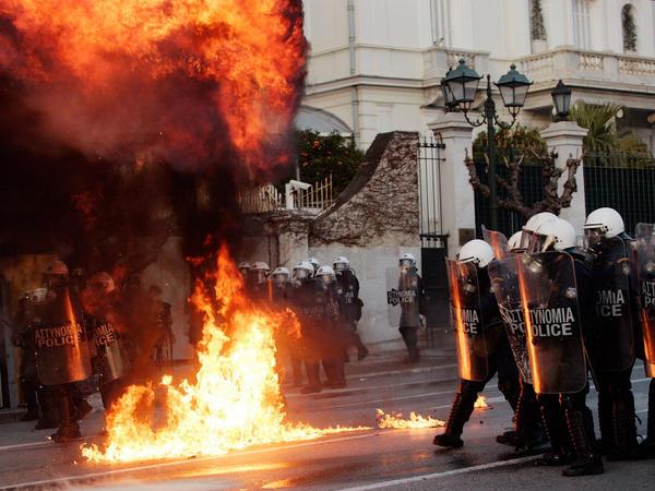 Greek demonstrators throw fire bombs towards riot police during violent protests in central Athens on February 12.