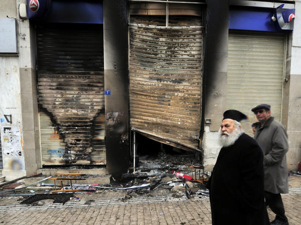 A Greek priest walks past a burned branch of the Eurobank in central Athens on February 13.