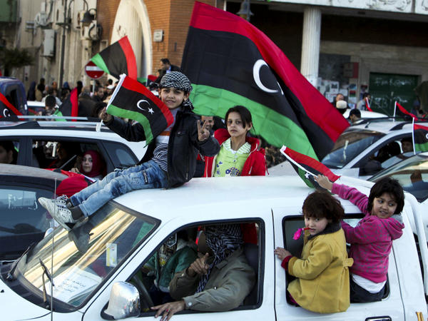 Children in Tripoli, Libya, wave a national flag from a car as people celebrate the one-year anniversary of the beginning of Libya's revolution, Feb. 16 2012.
